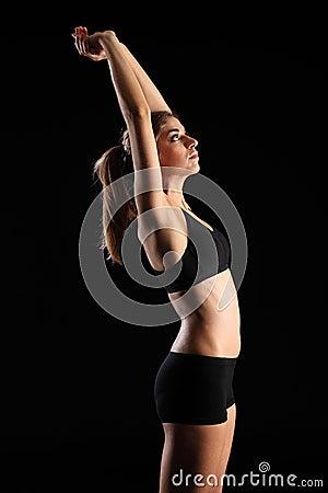 Vrouw in sportenuitrusting het uitrekken zich wapens boven hoofd