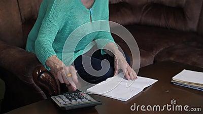 Vrouw telt op een rekenmachine en schrijft in een notebook stock video