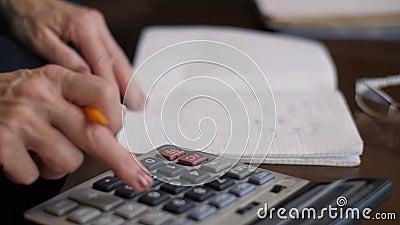 Vrouw telt op een rekenmachine en schrijft in een notebook stock footage