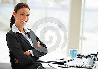 Vrouw in zwarte kostuumzitting in bureau
