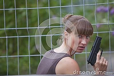 Vrouwelijke agent met kanon het verbergen
