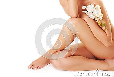 Vrouwelijke benen met witte orchidee