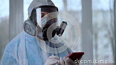 Vrouwelijke Doctor Bezig met het dragen van een masker en Suit-zandinformatie via mobiele telefoon Medische drager draagt een bes stock videobeelden