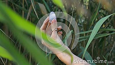 Vrouwelijke hand met een amethyst kristal yoni-ei op rivierachtergrond Gezondheid van vrouwen, eenheid met natuurbegrippen stock video