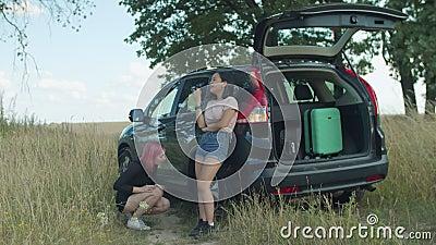 Vrouwelijke reizigers die vlakke band controleren op auto stock video