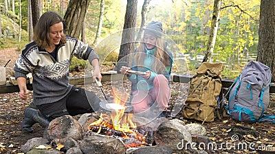 Vrouwelijke vrienden koken traditionele pannenkoeken boven een open vuur in het kamp buiten tijdens een heup stock footage