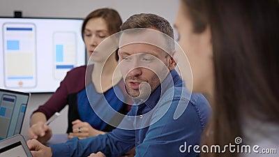 Vrouwen en mensen bespreken in het kantoor van de ontwikkeling van mobiele apps tijdens zakelijke vergaderingen stock videobeelden