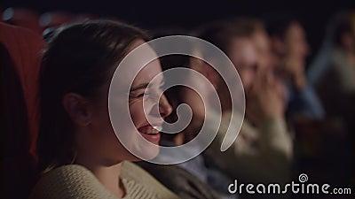 Vrouwengezicht die op grappige film letten bij bioskoop Bioskoopmensen die komedie op film letten stock videobeelden