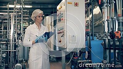 Vrouweningenieur, fabrieksarbeider controleert machines in een moderne fabriek Vrouwelijke werknemers controleren de kwaliteit va stock videobeelden