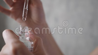 Vrouwenpalm opent een fles met een pipet Natuurlijk gelaatsserum Druppels van essentiële vloeistofval van een druppel stock videobeelden
