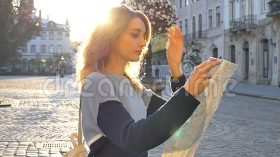 Vrouwenportret van een vrouw met een zonnebril en een papieren kaart in haar handen, die vroeg in de richting op zoek is stock footage