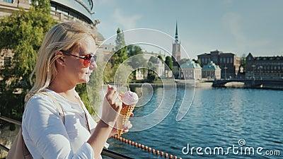 Vrouwentoerist die roomijs op de achtergrond van de herkenbare mening van de stad van Stockholm in Zweden eten stock video