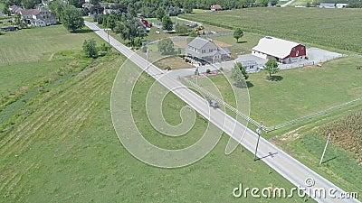 Vue aérienne d'un Cheval Amish et d'une descente en voiturette dans la campagne Amish pendant une journée d'été banque de vidéos