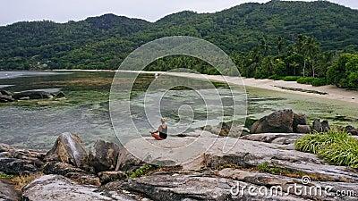 Vue aérienne d'une jeune fille bronzée blonde méditant sur un rocher de granit sur une plage tropicale exotique sur l'île paradis banque de vidéos