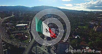 Vue aérienne de bourdon d'un drapeau mexicain énorme ondulant dans la vue panoramique arrière quelques banlieues et montagnes Les banque de vidéos