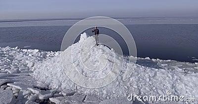Vue aérienne de dron du jeune homme heureux actif restant sur les glaciers de glace près du littoral de la main de tissage de mer banque de vidéos