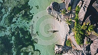 Vue aérienne de 4K haut en bas de la célèbre Anse Source d`Argent plage tropicale à la lumière du jour ensoleillée Lagon peu prof banque de vidéos