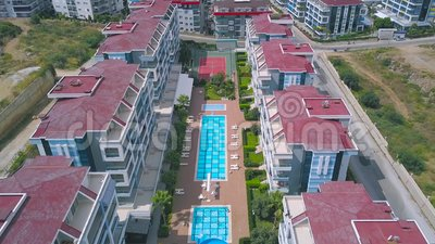 Vue aérienne en haut des hôtels avec piscine d'eau bleue entourée d'autres bâtiments et pelouse verte Art clips vidéos