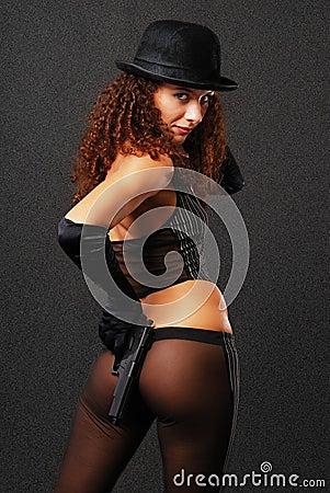 Vue arrière de bandit sexy cachant un pistolet.