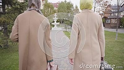 Vue arrière de deux amies caucasiennes matures en manteau beige, foulard et lunettes de soleil prenant de vieux sacs de voyage et banque de vidéos