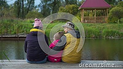 Vue arrière de la famille assise sur la jetée en automne clips vidéos