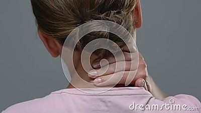 Vue arrière de la femme massant douloureusement le cou, ressentir de fortes douleurs, problème de santé banque de vidéos