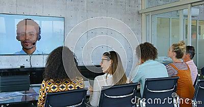 Vue arrière des cadres commerciaux de métis faisant la vidéoconférence dans le bureau moderne 4k banque de vidéos