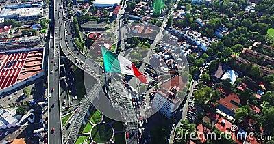 vue Bourdon-aérienne d'un drapeau mexicain énorme flottant, juste extérieur Mexico Une route et quelques banlieues dans le dos PR banque de vidéos