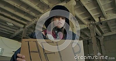 Vue d'en bas d'une fille sans abri du Caucase en vêtements sales levant le carton d'aide et regardant la caméra Affamé clips vidéos
