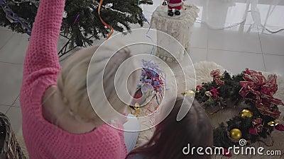 Vue d'en haut de la femme blonde adulte et de la petite brunette assise sur la moquette moelleuse et choisissant les décorations  banque de vidéos