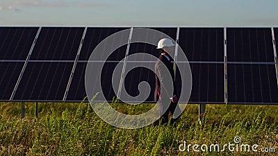 Vue de côté du directeur à énergie solaire de station marchant et vérifiant les panneaux photovoltaïques banque de vidéos