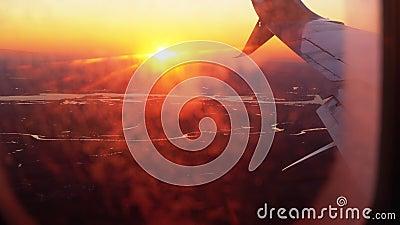 Vue depuis la fenêtre de l'avion sur l'aile pendant le coucher du soleil banque de vidéos
