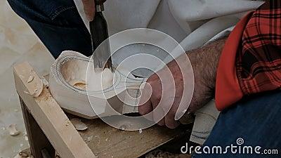 Vue du haut des mains d'un artisan avec des outils pour faire une cuillère en bois faite à la main Un sculpteur de bois travaille banque de vidéos