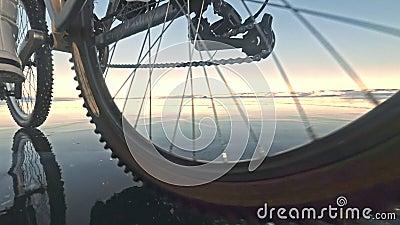 Vue du pneu Actioncam du tir 60fps La femme monte la bicyclette sur la glace Glace du lac Baïkal congelé Les pneus banque de vidéos