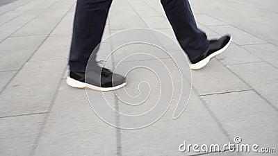 Vue du profil depuis le rez-de-chaussée des hommes en baskets grises marchant le long du trottoir banque de vidéos