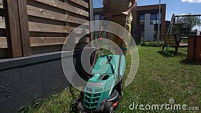 Vue en bas de l'angle du jeune homme tondant la pelouse à la maison Mouvement de Gimbal en arrière banque de vidéos
