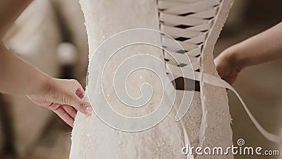 Vue en gros plan de jeune femme choisissant une robe de mariage dans la boutique Assistant aidant au laçage femelle sur le dos banque de vidéos