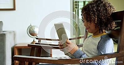 Vue latérale d'un garçon afro-américain jouant au jeu sur une tablette numérique sur sa chaise dans le hall de l'hôpital 4k clips vidéos