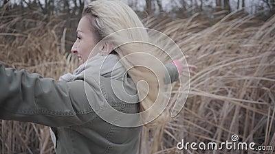 Vue latérale d'une jeune femme attirante debout dans le vent Une jeune fille du Caucase blond profitant de la journée d'automne g banque de vidéos