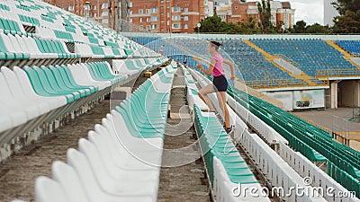 Vue latérale d'une jeune fille qui courait à l'étage d'un stade banque de vidéos