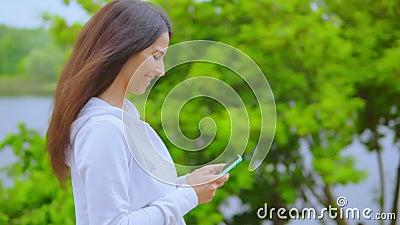 Vue latérale sur la fille en utilisant un smartphone marchant le long de la rivière banque de vidéos