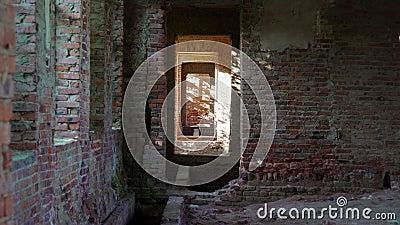 Vue par la porte dans le couloir étroit avec la correction ensoleillée sur le mur en pierre nu banque de vidéos