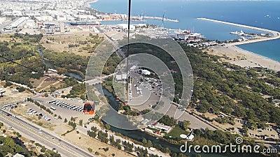 Vue sur le parc, le port, la rivière, l'autoroute avec voitures et le parking avec bus depuis la cabine de téléphérique d'Antalya banque de vidéos