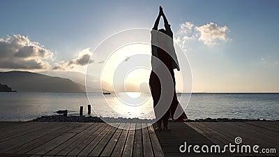 Vuxen kvinna som gör andlig övning nära havet på soluppgång i ultrarapid stock video