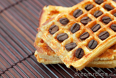 Waffles and coffee  beans on a bamboo mat