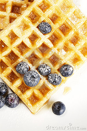 Waffles with sugar covered blueberries and syrup f
