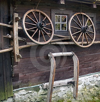 Wagon wheel on old log house
