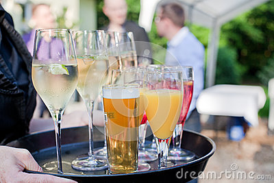 Waiter with dish of champagne, cocлtails, beer