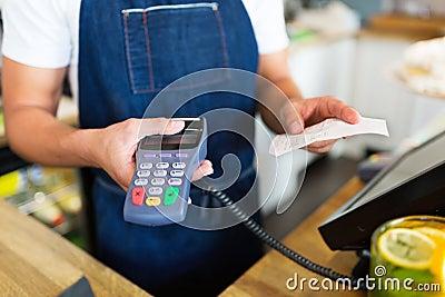 Waiter holding credit card reader Stock Photo