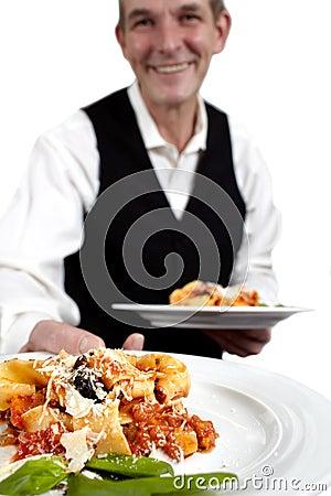 Waiter serves pasta